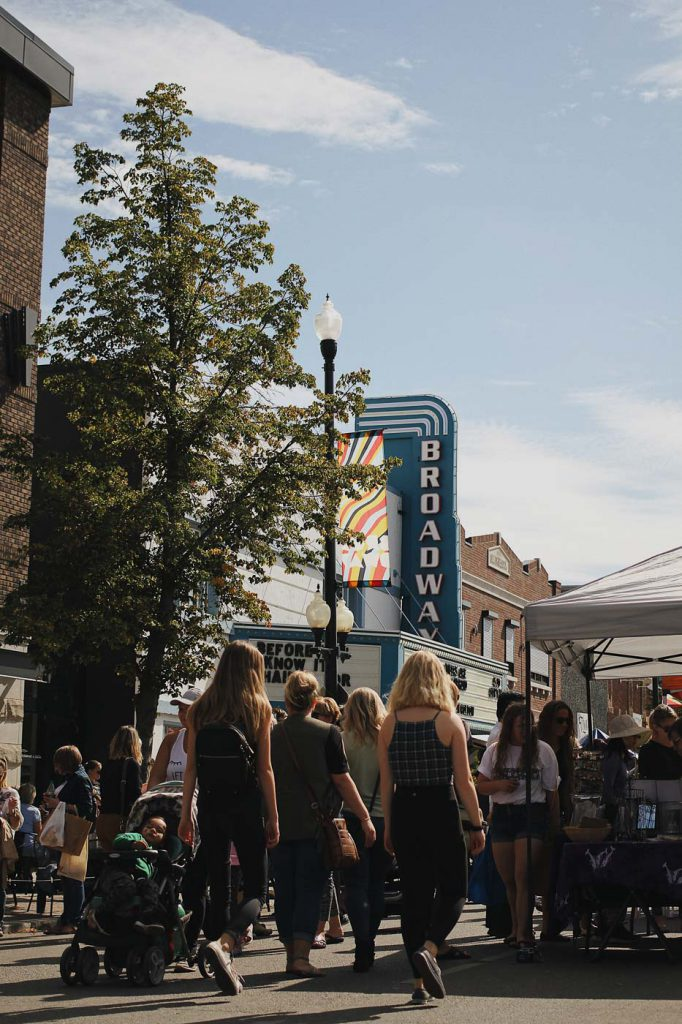 A crowd walking down Broadway Avenue in Saskatoon, with the Broadway Theatre sign visible.