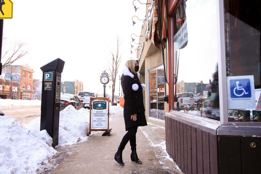 A blonde woman with a black mask on, wearing a black ski jacket with a white hood and pom poms, looks into the window of a building on Broadway Avenue in Saskatoon. It's winter and snow lines the street.